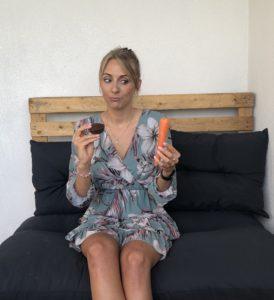 jeune femme hésitant entre un gâteau au chocolat et une carotte