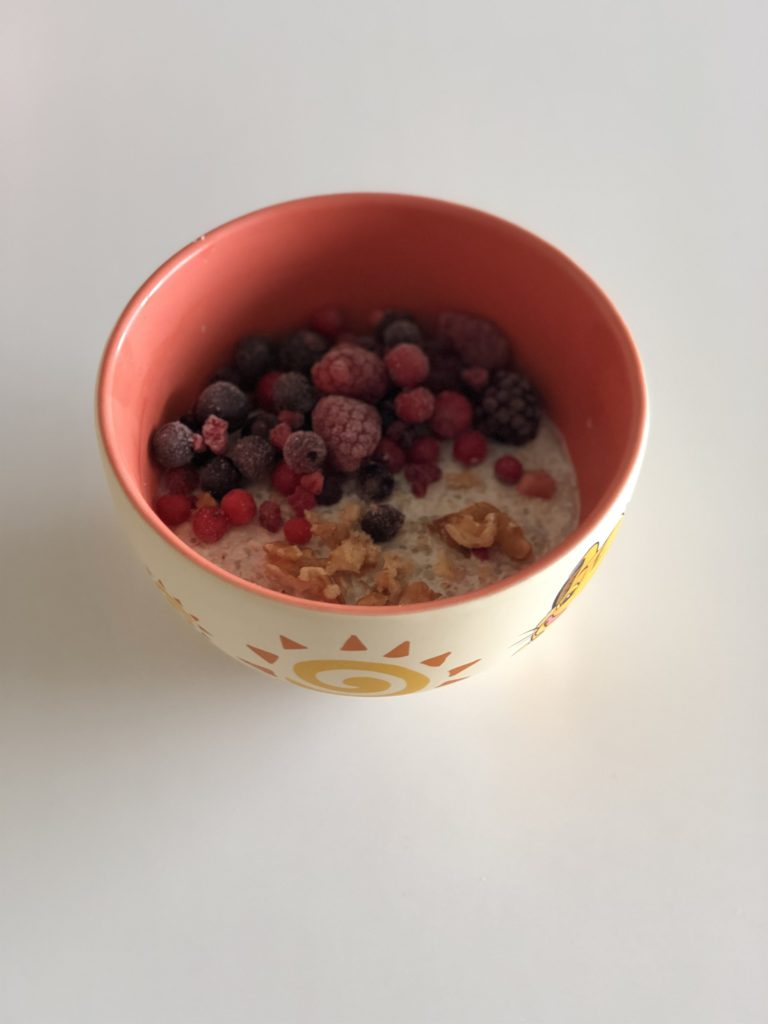 overnight porridge. Un bol, du lait, des flocons d'avoine, des fruits rouges, des noix, des graines de chia