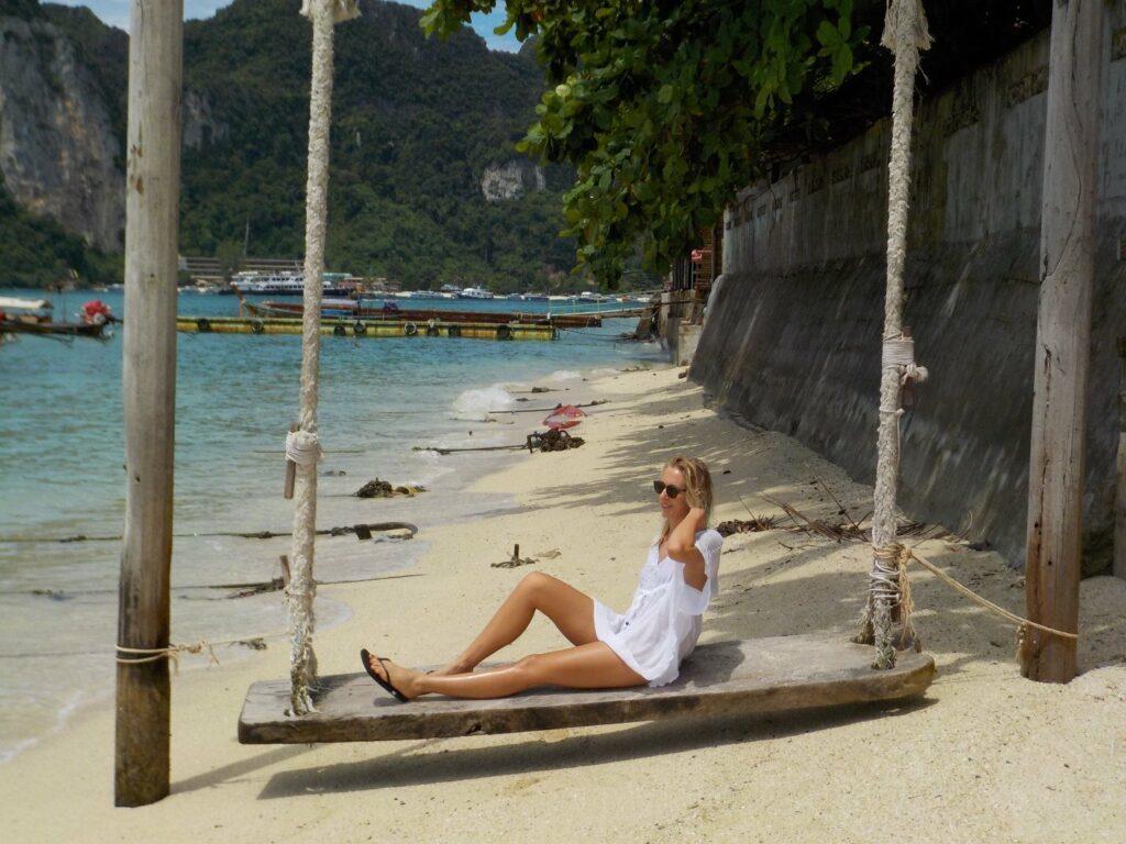 Jeune femme assise sur un banc au bord de la plage