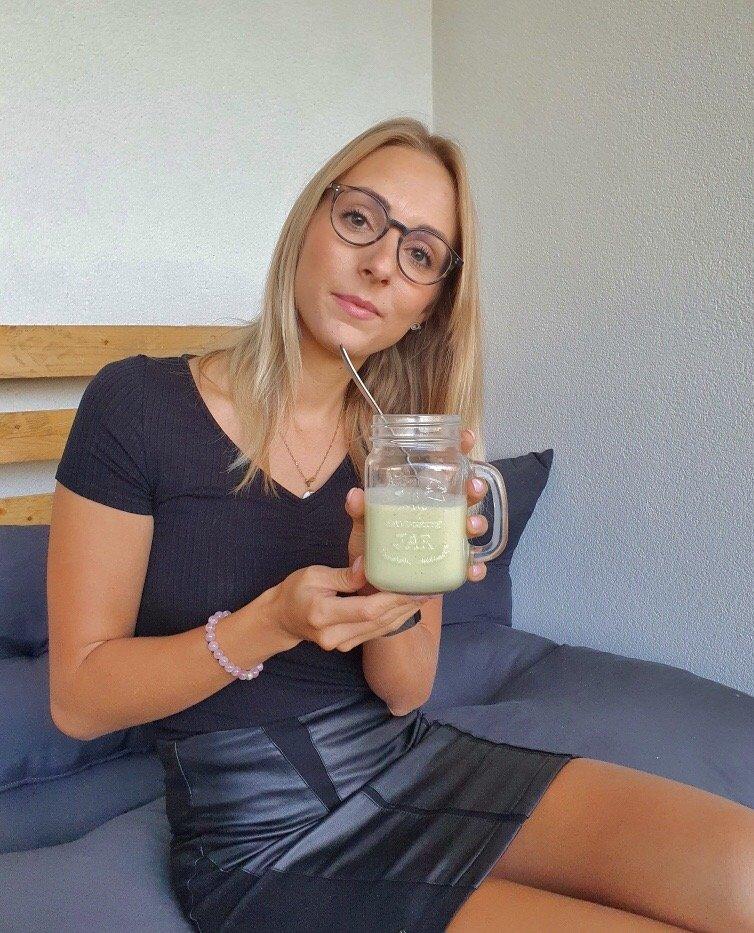 Femme qui boit un smoothie vert à base d'avocat et de banane avec du lait végétal