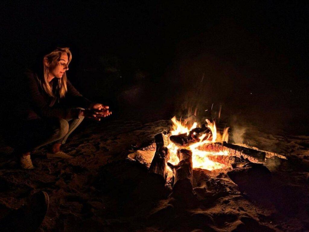 Femme blonde autour d'un feu de camp