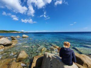 femme assise sur un rocher en face de la mer